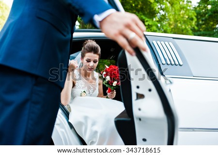 Groom open door of limousine and take hand to bride - stock photo