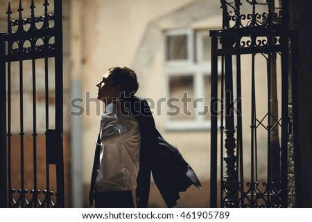 groom  posing for photographer at the high gates