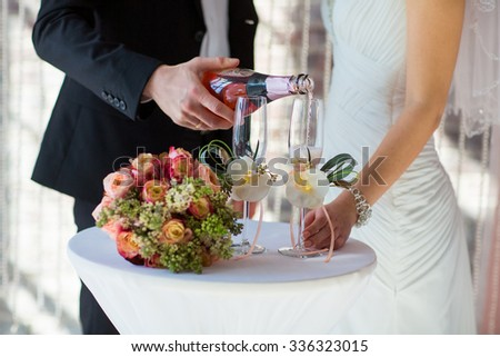 Groom pouring for bride champagne into the glass - stock photo