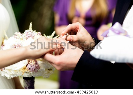 Groom puts a wedding ring on bride's delicate finger - stock photo