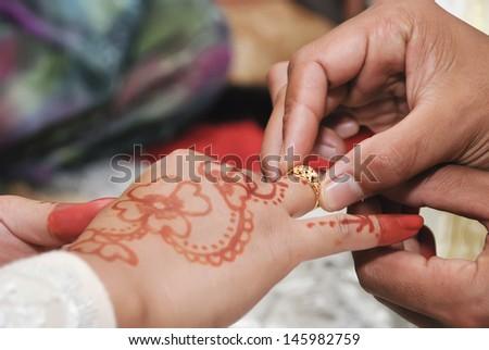 Groom Puts Wedding Ring on Bride Finger - stock photo
