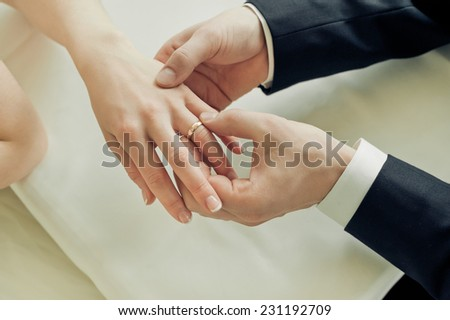 Groom putting a ring on bride's finger during wedding ceremony - stock photo