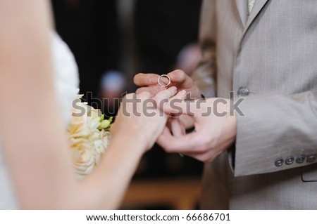 Groom putting a wedding ring on bride's finger - stock photo