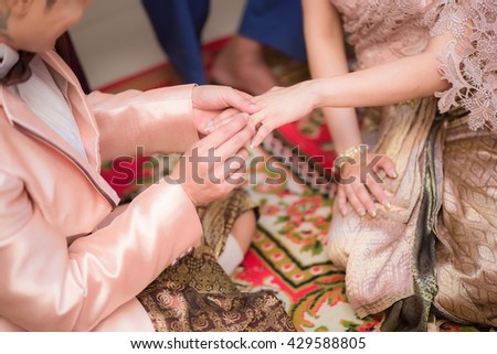 groom putting a wedding ring. Thai wedding