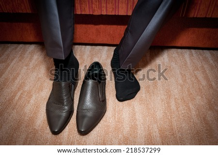 groom putting on black shoes at home - stock photo