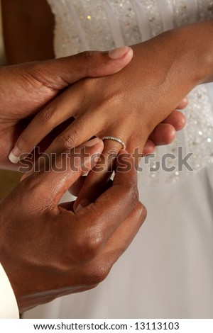Groom putting on wedding ring - stock photo