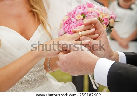 groom putting ring on bride's finger, wedding - stock photo