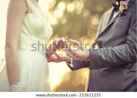 Groom putting the wedding ring on bride's finger - stock photo