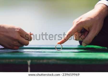 groom rolling wedding ring to bride - stock photo