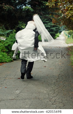 groom running away with bride on his back outdoors in park alley