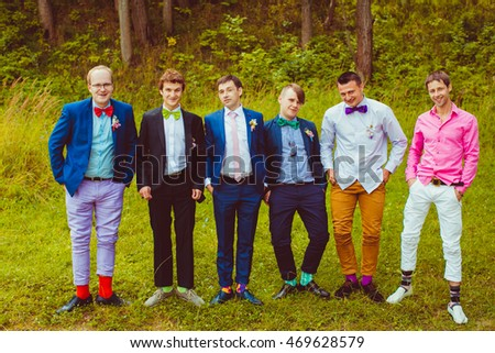 Groom's band surround him while posing in the wood