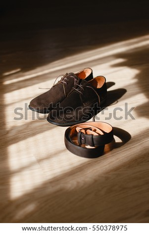 Groom's brown stylish shoes and leather belt lying on the wooden floor in the rays of light. Groom's morning details in the fine art style.