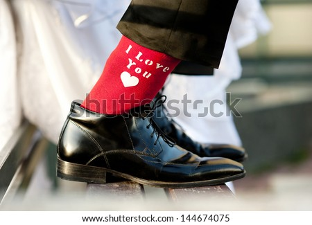 Groom's funny feet with love sign on red socks. - stock photo