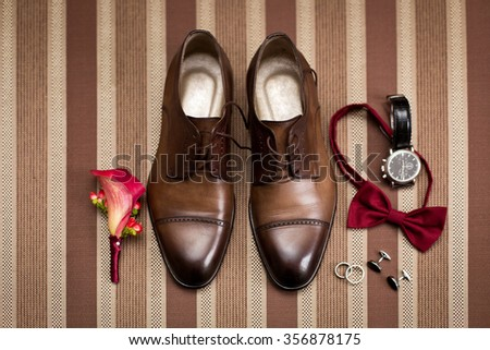 Groom's morning. Wedding accessories in red colors. Tie-butterfly, shoes, rings, boutonniere - stock photo