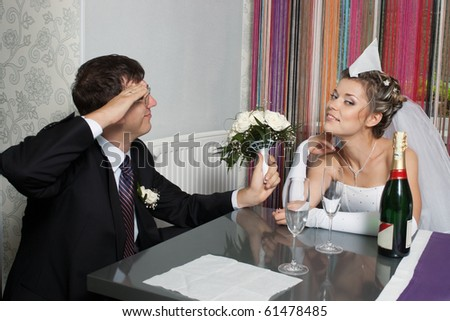 Groom saluting bride with paper garrison cap sitting at table with champagne and glasses