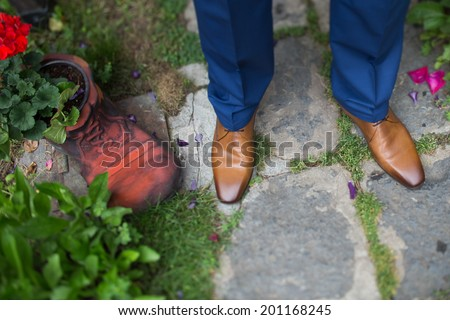 groom shoes close up near a dwarf shoe  filled with geranium - stock photo