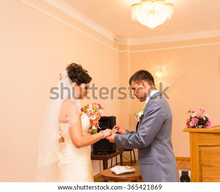 Groom slipping ring on finger of bride at wedding - stock photo