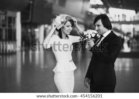 Groom smells a wedding bouquet standing behind a bride in the airport terminal