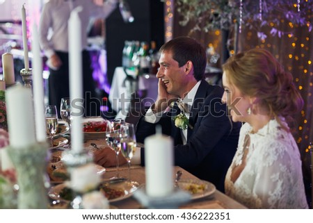 Groom smiles holding his head with a hand and sitting behind a bride - stock photo