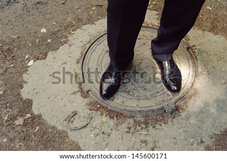 groom standing on hatchway in black shoes - stock photo