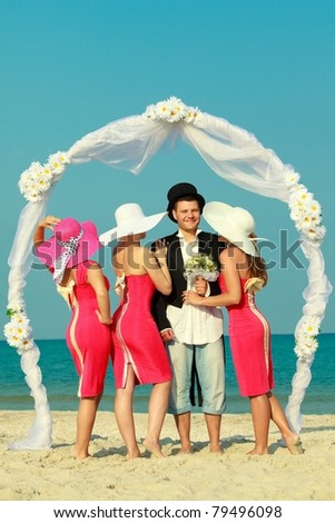 Groom standing with bridesmaids under archway on beach - stock photo