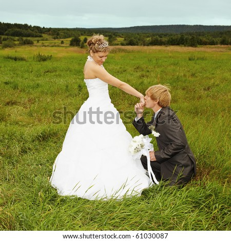 Groom to genuflect near the bride and kisses to it a hand - stock photo