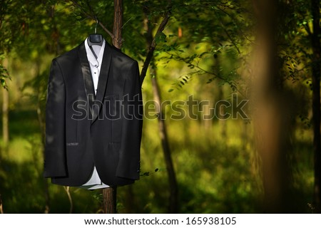 Groom tuxedo hanged in a tree, nature - stock photo