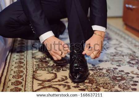 groom tying cord on his wedding shoe - stock photo