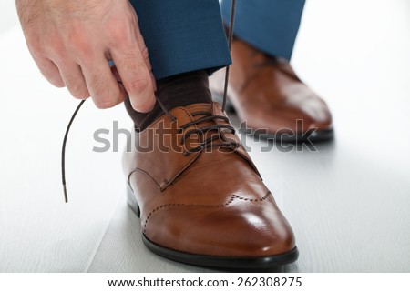 groom tying shoe laces - stock photo