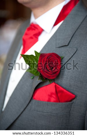 groom wearing red rose buttonhole at wedding - stock photo