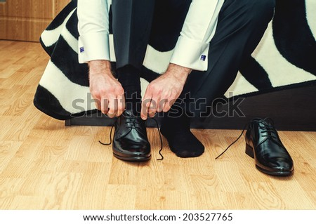 Groom wearing shoes on wedding day, tying the laces and preparing. Business man dressing up with classic, elegant shoes