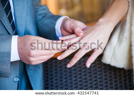 groom wears a ring on a finger of his beloved