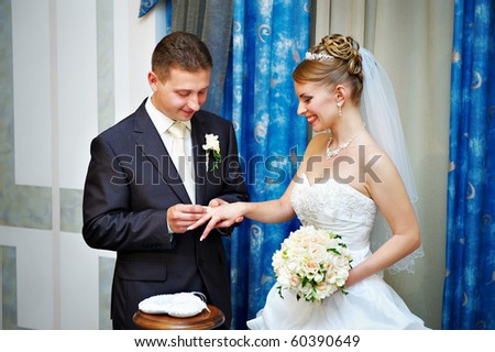 Groom wears a wedding ring a happy bride. Solemn registration of marriage. - stock photo