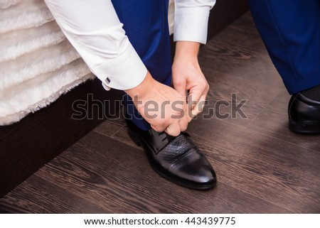 groom wears nice shoes and tying shoelaces - stock photo