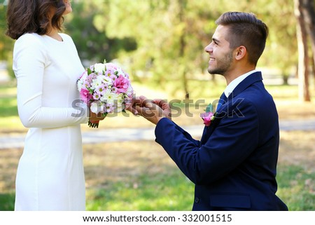 Groom wears ring bride outdoors - stock photo