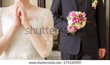 groom with a bouquet in hand goes to the bride - stock photo