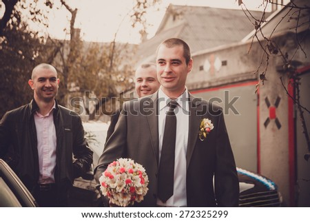 Groom with best man and groomsmen  go to the bride at wedding. Repayment of the bride. Russian custom. - stock photo