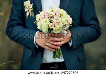 Groom with bridal bouquet - stock photo