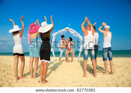 Groom with bride wearing lei, standing under archway on beach and  their friends applauding for joy - stock photo