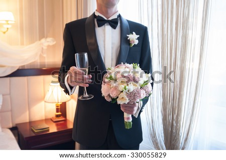 groom with flowers and glass of champagne in  his hands - stock photo