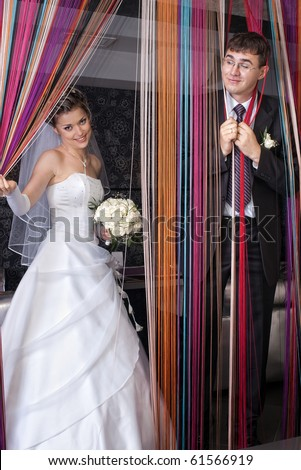 groom with funny expression and bride behind colored thread curtain