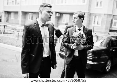 Groom with groomsman background wedding cars