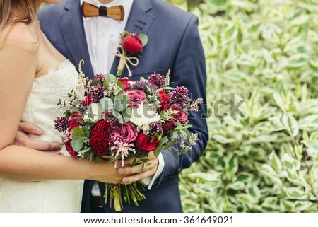 groom with wooden bow-tie and red boutonniere hug bride with lilac wedding bouquet - stock photo