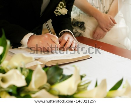 groom  write on registration of marriage - stock photo