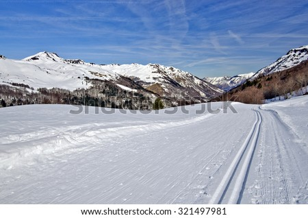 Groomed Cross Country ski trail in Somport ski resort, the Aspe Valley is in perspective, Bearn, Atlantic Pyrenees, border of France and Spain - stock photo