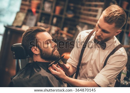 Grooming of real man. Side view of young bearded man getting beard haircut at hairdresser while sitting in chair at barbershop - stock photo