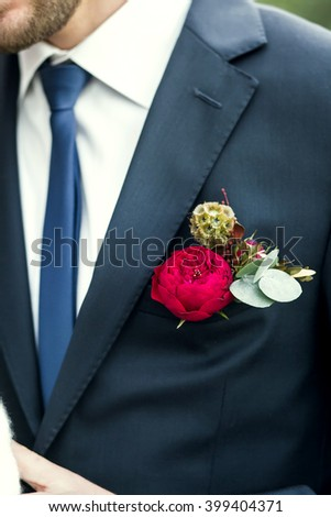 grooms with blue tie and red rose boutonniere on wedding day