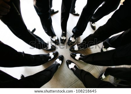 Groomsmen Creating a Circle with Their Legs - stock photo