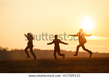 Groomsmen playing fool in the rays of sunset somewhere on the field