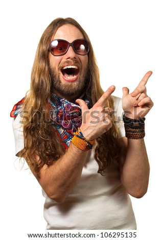 Groovy and happy young man dressed like a hippie pointing at copy-space. Isolated on white. - stock photo